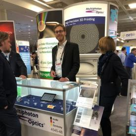 Fabian Hilbert, MPO, attending visitors at the Multiphoton Optics Booth in Photonics West, where the results of nanostructured flat microoptics were exhibited.